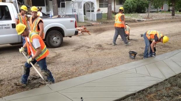 A Regina crew builds a sidewalk on the city's south side. Homeowners on this street will have to pay for most of it under the city's local improvement program.
