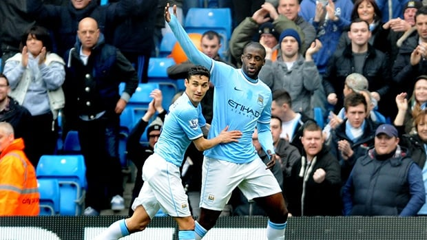 Manchester City's Yaya Toure, right, celebrates with teammate Jesus Navas after scoring from the penalty spot against Southampton on Saturday.