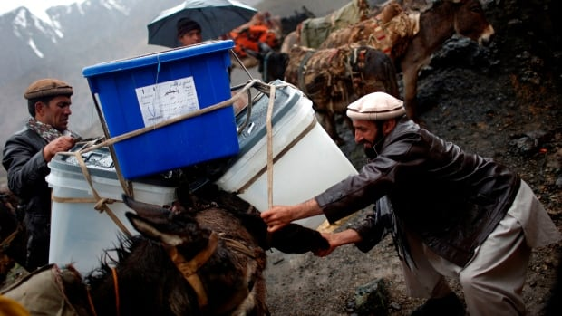 An Afghan man loads ballot boxes and other election material on a donkey to be transported to polling stations which are not accessible by road.