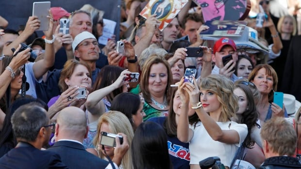 Pop music artist Taylor Swift takes a selfie with fans.