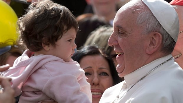 Pope Francis smiles as he holds a baby in Rome on April 6. On Monday, the Vatican announced the Institute for Works of Religion (Vatican bank) will remain in business.