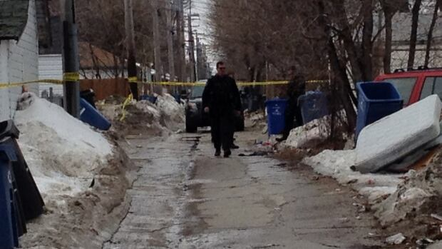 An officer walks down a taped off alley near Manitoba Avenue in Winnipeg after a teen boy was shot Monday afternoon.