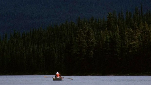 Boaters are dwarfed by a mountain peak while rowing on Maligne Lake, the largest lake in Alberta's Jasper National Park. Three former Parks Canada managers have written to the environment minister to oppose a proposed development on the lake.