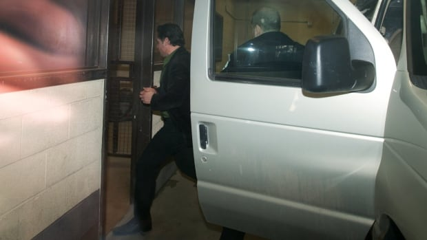 Suspended Senator Patrick Brazeau is escorted into the courthouse in Gatineau, Que., after being arrested early Thursday morning.