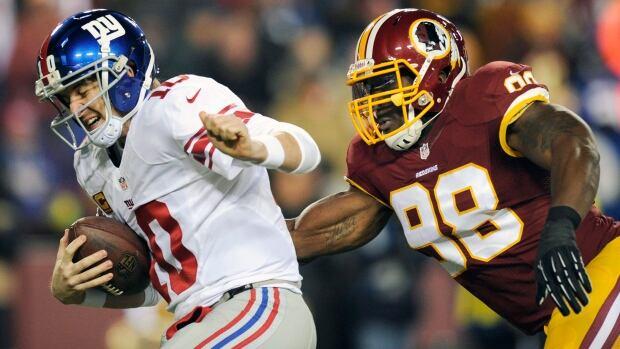 New York Giants quarterback Eli Manning, left, is sacked by Washington Redskins outside linebacker Brian Orakpo during a Dec. 13, 2013 game.