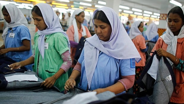 Workers sort clothes at a garment factory near the collapsed Rana Plaza building in Savar, Bangladesh. The April 24 collapse of the Rana Plaza complex, built on swampy ground outside Dhaka with several illegal floors, killed over 1,135 workers and focused international attention on lax safety standards