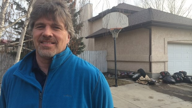 Darren Cannell says pieces of garbage from his neighbour's trash pile continually end up on his property.