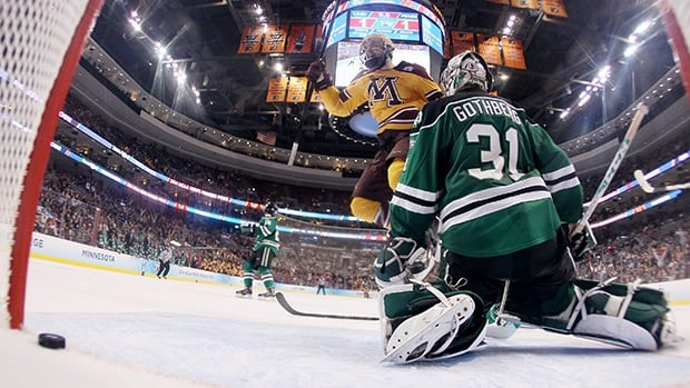 Seth Ambroz (17) of the Minnesota Golden Gophers celebrates teammate Justin Holl's goal with 0.6 seconds left in the game as goaltender Zane Gothberg (31) of the North Dakota Fighting Sioux looks on on Thursday in Philadelphia.