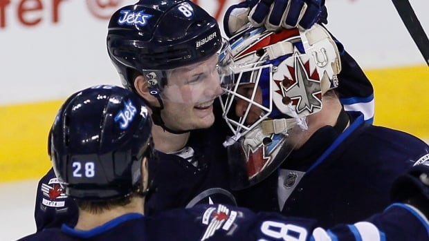 Winnipeg Jets goaltender Michael Hutchinson celebrates his first NHL win with Patrice Cormier and Jacob Trouba after topping all three Boston Bruins shooters in a shootout on Thursday. Jets won the game, their final home game of the season, 2-1.