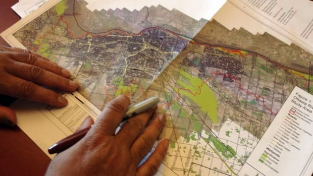 RVCA engineer Ferdous Ahmed goes over a older floodplain map for the City of Ottawa.