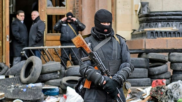 A masked armed man, representing Ukrainian special forces, stands guard outside the regional administration building in the eastern city of Kharkiv last week following  armed protests by pro-Russia demonstrators. The central government in Kyiv has now said it will mobilize the army to put down a rebellion by pro-Russia militants, a decision Moscow has taken to the UN Security Council.