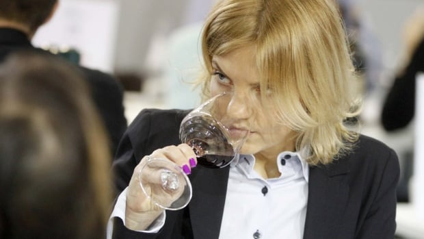A woman noses wine at the Vinitaly Exhibition
