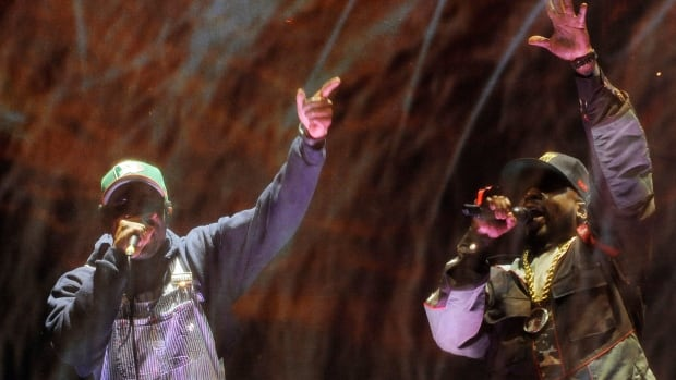 Andre 3000, left, and Big Boi of hip hop group Outkast perform behind a screen during their headlining set on the first day of the 2014 Coachella Music and Arts Festival on Friday in Indio, Calif.