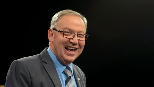 NDP leader Darrell Dexter sports a smile as he prepares to participate in a television broadcast in Halifax on Sept. 10, 2013.