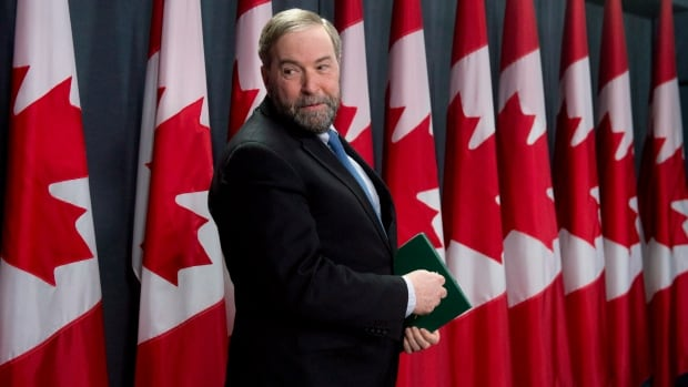 NDP leader Tom Mulcair looks over his shoulder as he arrives at a news conference Monday March 24, 2014 in Ottawa.