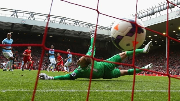 Philippe Coutinho of Liverpool scores the winner on keeper Joe Hart in a 3-2 victory over Manchester City at Anfield on Sunday.