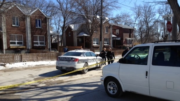 Winnipeg police in the 300 block of Alexander Avenue on Sunday. Police believe 27-year-old Geoffrey Oliver Reid was shot inside a home there on Saturday.