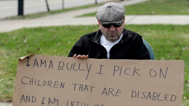Edmond Aviv sits on a street corner holding a sign declaring he's a bully, a requirement of his sentence because he was accused of harassing a neighbour and her disabled children for the past 15 years.