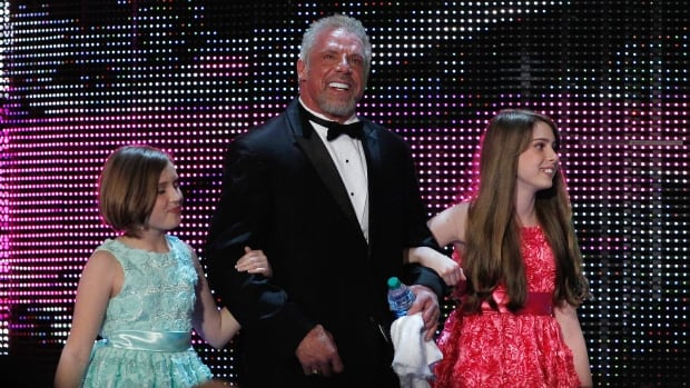 James Hellwig, a.k.a. The Ultimate Warrior, is escorted by his daughters to the stage during the WWE Hall of Fame Induction at the Smoothie King Center in New Orleans on April 5. He died three days later.