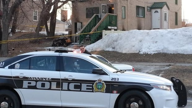 Police remain at the scene of a rooming house fire in Winnipeg, where one man died.