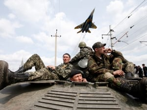On the eve of crucial four-power talks in Geneva on the former Soviet country's future, Ukrainian government forces and separatist pro-Russian militia staged rival shows of force in eastern Ukraine on Wednesday amid escalating rhetoric from Kyiv and Moscow. Here, a fighter jet flies above Ukrainian soldiers in Kramatorsk on April 16.