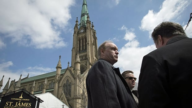 People line-up outside the Cathedral Church of St. James prior to the state funeral for the late Jim Flaherty in Toronto on Wednesday, April 16, 2014.