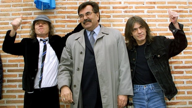 AC/DC's Angus (left) and Malcolm (right) Young, are seen in 2000 with Jose Luis Perez, mayor of the Madrid district of Leganes, at the inauguration of a street named after the group. The rock icons announced that Malcolm is taking break to focus on his health.