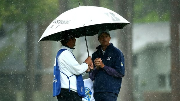 Matt Kuchar, right, and his caddie huddle under an umbrella during Friday's soggy second round at Harbour Town Golf Links.