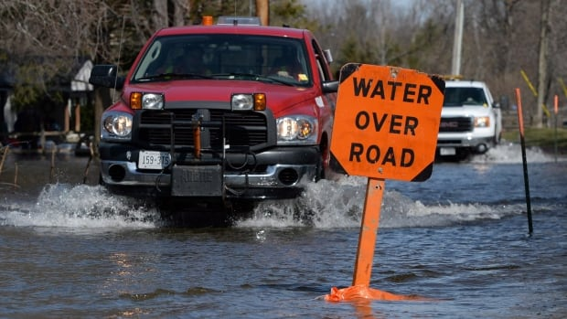 Municipal workers make their way along River Road north of Belleville, Ont. Water levels are currently decreasing, but the region still faces flooding over the Easter weekend.