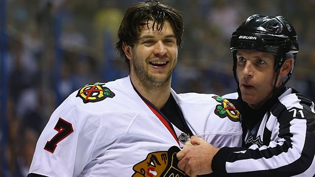 Referee Brad Kovachick restrains Brent Seabrook of the Chicago Blackhawks after his hit knocked David Backes of the St. Louis Blues, not pictured, out of Game 2 on Saturday in St. Louis, Missouri.