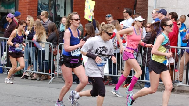 Tanya Carter, of Prince George, B.C., is seen (centre, in dark blue tank top) running in the 2013 Boston Marathon. She narrowly missed being in the blast zone when the two bombs went off.