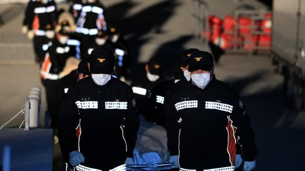The bodies of a passengers aboard the Sewol, a South Korean ferry that sank in the water off the southern coast, are carried by rescue workers upon arrival at a port in Jindo, South Korea, on Monday.