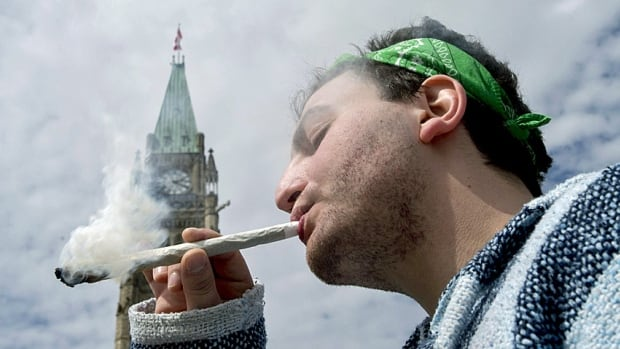 A man smokes a joint at the Fill the Hill marijuana rally on Parliament Hill in Ottawa on Sunday.