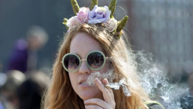 A woman smokes a joint at the Fill the Hill marijuana rally on Parliament Hill on Sunday, April 20, 2014. Health Canada issued a recall notice on Friday for a batch of medical marijuana produced in B.C., in what's believed to be the first recall of medical marijuana in Canada.