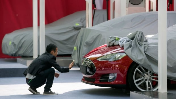 A man takes a photo of the logo on a Tesla Model S sedan at an event in Beijing, China, Tuesday. Tesla Motors delivered its first eight electric sedans to customers in China on Tuesday and Musk said the company will build a nationwide network of charging stations and service centres as fast as it can.