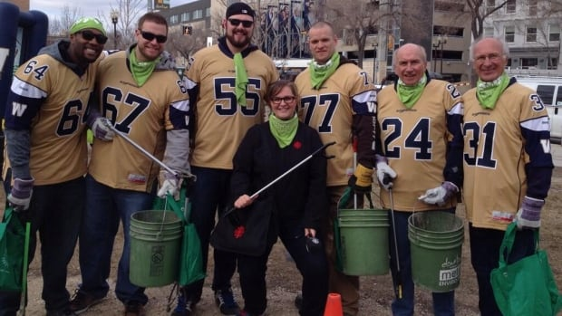 CBC Information Radio host Marcy Markusa is joined by current and past members of the Winnipeg Blue Bombers to clean parts of downtown Winnipeg on April 22.