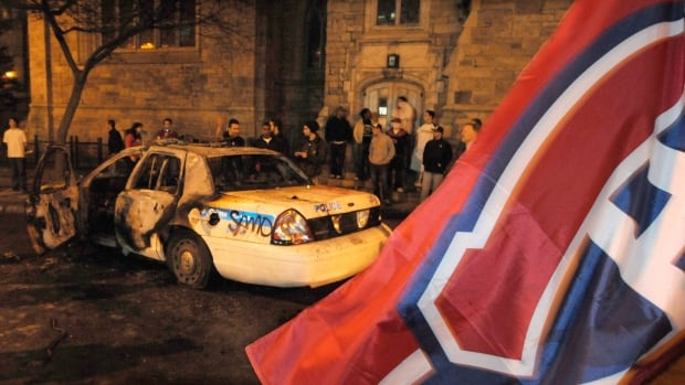 A burned-out police cruiser sits in downtown Montreal as violence erupted following the Montreal Canadiens' elimination of the Boston Bruins in game seven of the first round of the Stanley Cup playoffs on April 21, 2008.