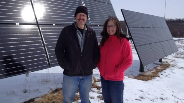 Bev and Will Eert stand beside their solar array at their home about 40 kilometres southwest of Portage la Prairie, Man.
