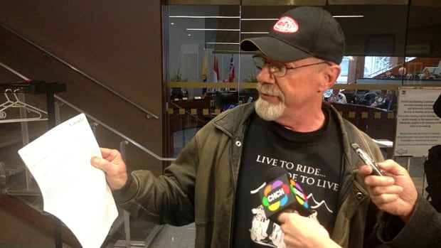 Norm Dorr holds up a copy of the Canadian Charter of Rights and Freedoms outside a Hamilton Police Services board meeting last month after the board denied his request to speak. Dorr has attended every board meeting since September, inspiring a number of procedural changes. He's going to at least stop for the summer, he says.