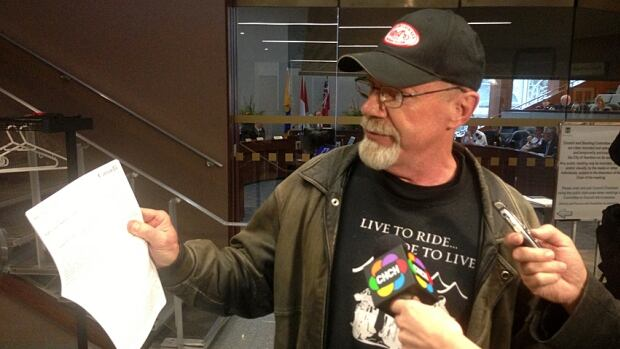 Norm Dorr holds up a copy of the Canadian Charter of Rights and Freedoms outside a Hamilton Police Services board meeting. The board is examining its policy for public deputations after Dorr made a public presentation last month calling for Chief Glenn De Caire's resignation.