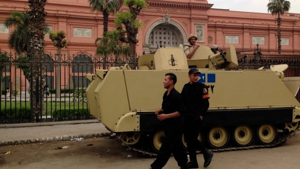 Police and soldiers stand guard in front of the Egyptian Museum in Tahrir square in Cairo. Attacks against Egyptian police and military have stepped up as militant groups wage an increasingly violent campaign following the ouster of Islamist President Mohammed Morsi.