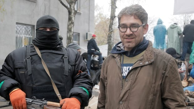 In this photo taken last Sunday, Vice News reporter Simon Ostrovsky, right, stands next to a pro-Russian gunman at a seized police station in the eastern Ukraine town of Sloviansk. Pro-Russian insurgents in eastern Ukraine confirmed Wednesday they are holding him captive in a seized Ukrainian security service building.