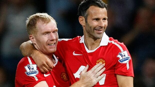 Interim Manchester United coach Ryan Giggs, right, seen here with teammate Paul Scholes during a Aug. 16, 2010 match. Scholes will assist Giggs along with fellow ex-teammates Nicky Butt and Phil Neville following the dismissal of David Moyes.