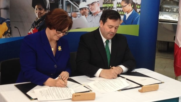 Theresa Oswald, Manitoba's jobs and economy minister, signs the province's Canada Job Grant agreement on Wednesday with federal Employment Minister Jason Kenney in Winnipeg.