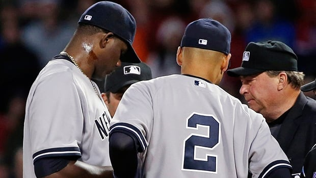 Home plate umpire Gerry Davis, right, confers on the mound with New York Yankees starting pitcher Michael Pineda, left; shortstop Derek Jeter (2); and others in the second inning at Fenway Park in Boston on Wednesday. Pineda was ejected after umpires found with a foreign substance on his neck.