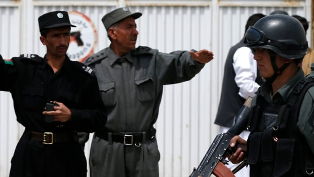 Afghan policemen stand outside Cure Hospital after three American doctors were killed in Kabul on Thursday when a security guard opened fire at the international hospital.