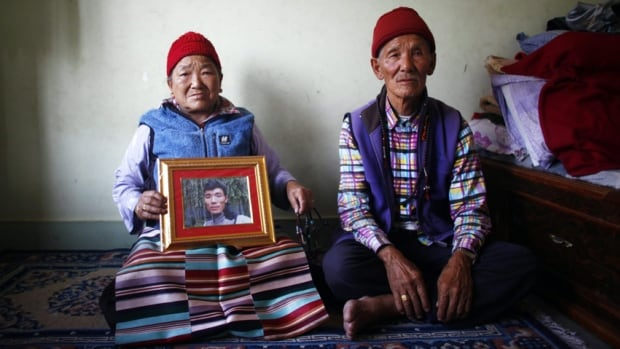 Nimdige Sherpa holds a portrait of her son Ang Kaji Sherpa, killed in an avalanche on Mount Everest, with her husband Ankchu Sherpa seated beside her. While the season has not been officially cancelled, guides and Sherpas said it appeared increasingly unlikely that any summit attempts would be made this season from the Nepal side of the mountain.