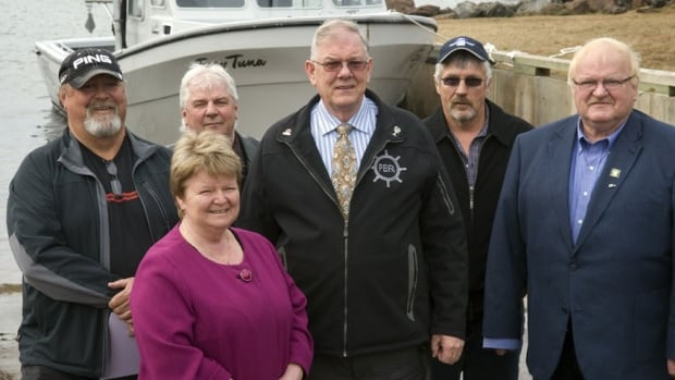 Federal fisheries Minister Gail Shea and P.E.I. Fisheries Minister Ron MacKinley pose with P.E.I. Fisheries Association board members Wayne Campbell, Bobby Jenkins, Mike McGeoghegan at an announcement of government funding for the halibut industry.