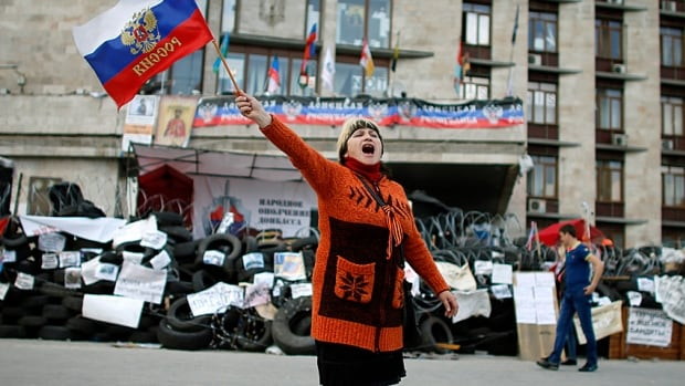 A pro-Russia protester shout slogans and waves a Russian flag outside the regional government building in Donetsk, barricaded by anti-Kyiv protesters, in Eastern Ukraine.