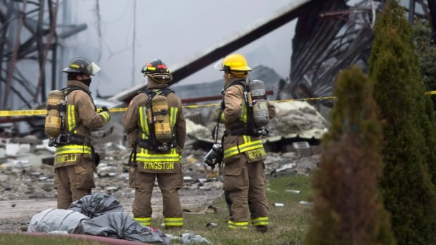 Firefighters watch an industrial fire in Mississauga, Ont. One firefighter was sent to hospital in critical condition and three others were injured while fighting the three-alarm blaze.